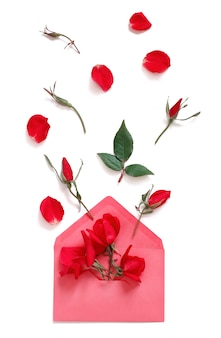 Composition de printemps avec enveloppe et roses rouges sur fond blanc vue de dessus