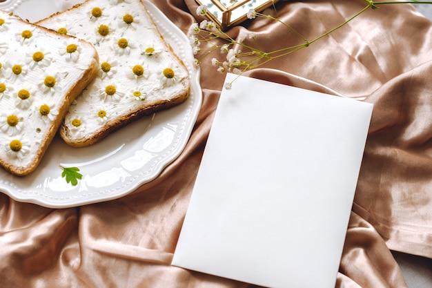 Composition de printemps, papier blanc blanc, sandwich au pain grillé avec des fleurs de camomille dans une assiette blanche