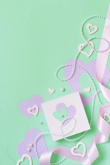 Composition de printemps avec roses, pétales, coeurs et boîte-cadeau sur fond pastel