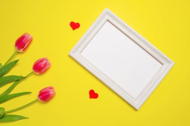 Composition de printemps avec des tulipes sur fond rose, cadre photo pour insérer vos informations.
