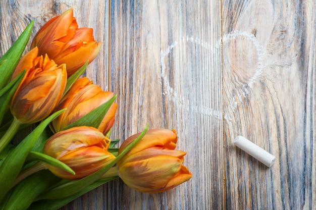 Composition de printemps avec des tulipes orange, craie et dessin de coeur