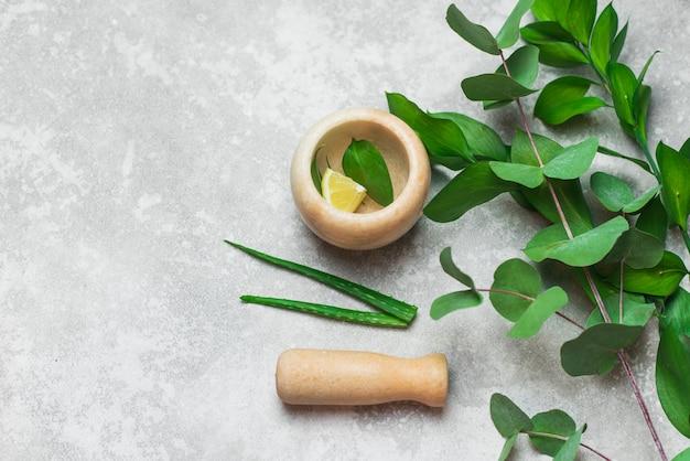 Composition avec des produits cosmétiques, mortier et pilon, feuilles et citron