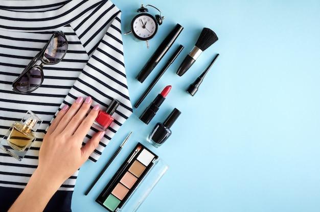 Composition de produits de maquillage différents avec la main sur fond bleu