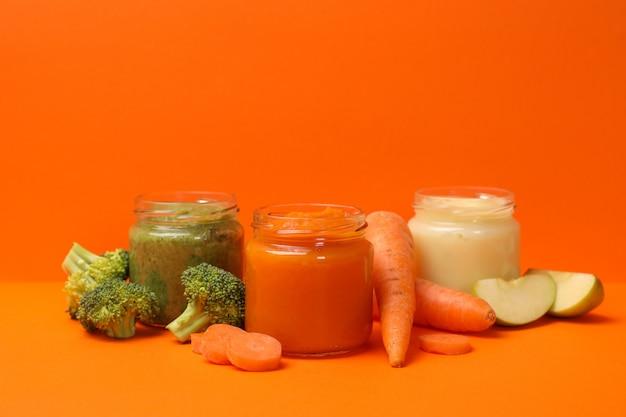 Composition avec purée de légumes sur fond orange. nourriture pour bébés