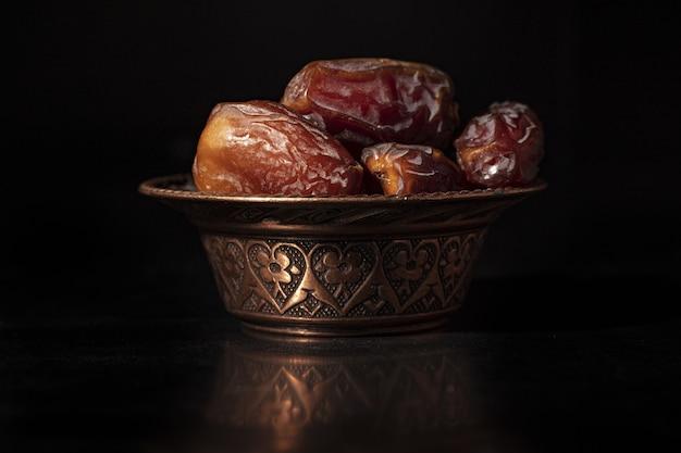 Composition de ramadan avec des dattes séchées sur une surface noire