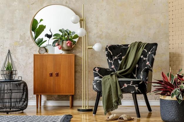 Composition rétro moderne de l'intérieur du salon avec fauteuil design, lampe, pouf en rotin, plantes, miroir, décoration, tapis et accessoires personnels élégants dans le concept wabi sabi.