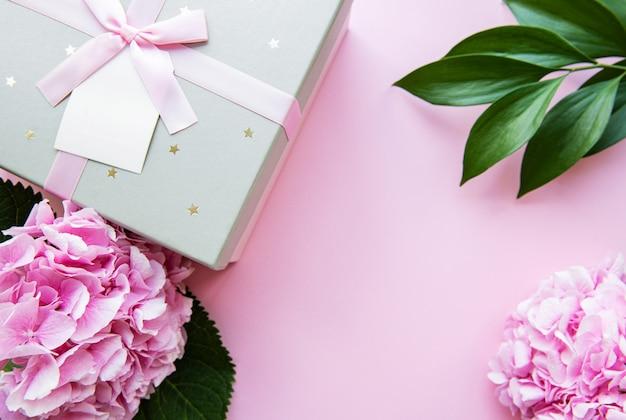 Composition romantique avec une boîte cadeau en argent avec un arc et des fleurs d'hortensia dans des couleurs roses, vue de dessus