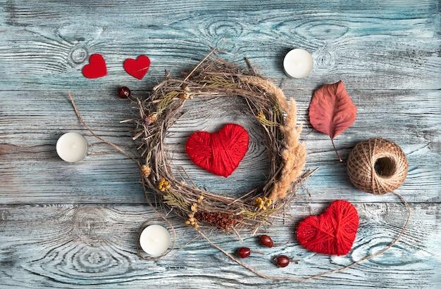 Composition romantique avec des coeurs rouges, une couronne et des bougies sur un fond en bois naturel.
