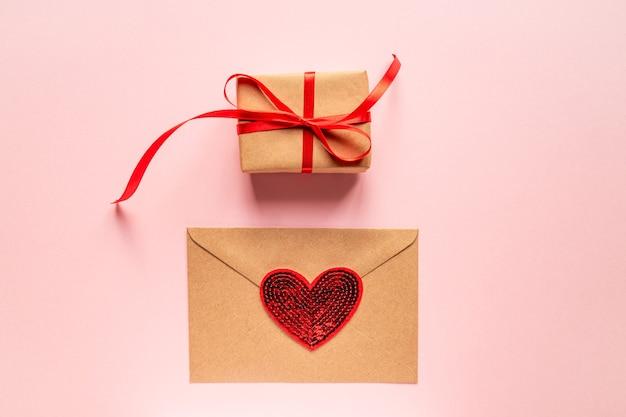 Composition romantique créative de la saint-valentin à plat vue de dessus laïque amour célébration de vacances avec enveloppe en papier, coeur rouge et boîte-cadeau