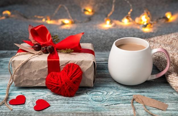 Composition romantique avec une tasse de café et un cadeau sur un fond cosy festif.