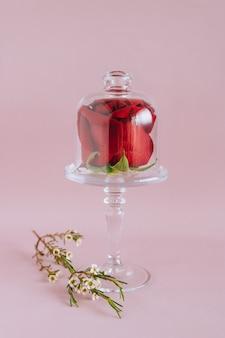 Composition de rose rouge sur un support à gâteau en verre, composition de tendances