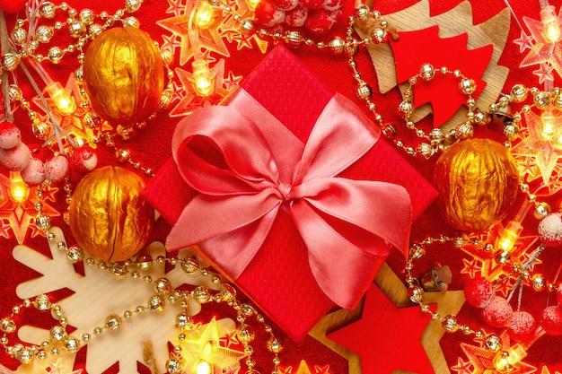 Composition rouge et dorée avec décorations de noël, guirlandes et coffret cadeau actuel avec ruban de satin.