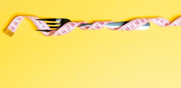 Composition d'un ruban à mesurer enroulé et d'une fourchette sur fond jaune. notion de surpoids.