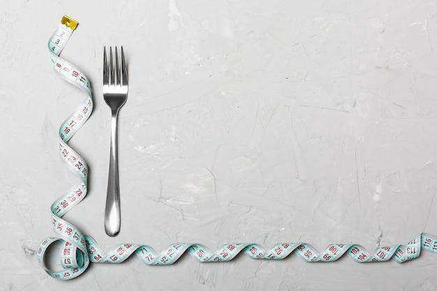Composition de ruban à mesurer recourbé et une fourchette