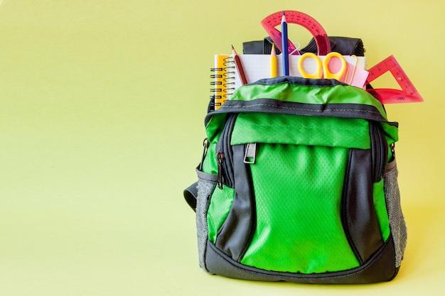 Composition avec sac à dos et fournitures scolaires sur jaune