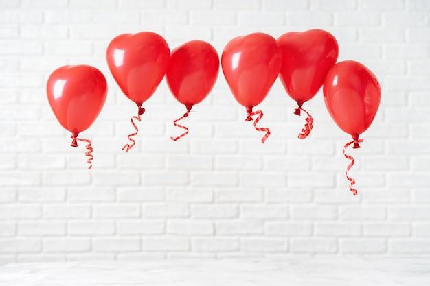 Composition de saint valentin avec des ballons rouges sur blanc