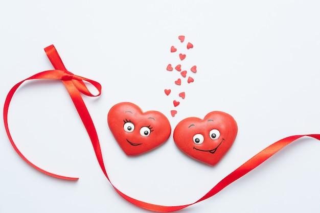 Composition de la saint-valentin. biscuits sucrés rouges en forme de coeurs amoureux de l'arc. modèle, arrière-plan. vue de dessus. mise à plat. espace copie