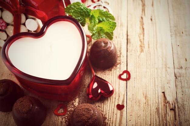 Composition de la saint-valentin avec des bonbons au chocolat, des bougies et des coeurs sur une surface en bois vintage. photo tonique avec espace de copie pour le texte