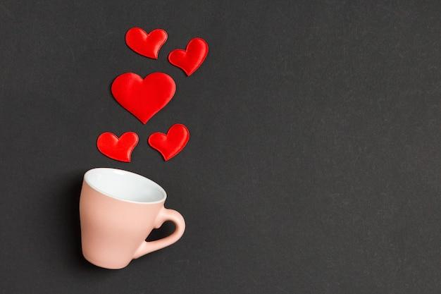 Composition de la saint-valentin de coeurs rouges tombant d'une tasse