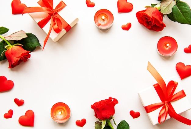 Composition de la saint-valentin avec des feuilles, des bougies et des coeurs