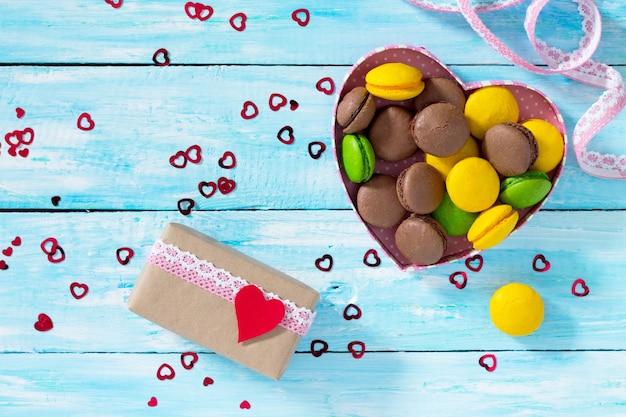 Composition de la saint-valentin avec des macarons dans un bol en forme de coeur et une boîte-cadeau sur une table en bois bleue. vue de dessus.