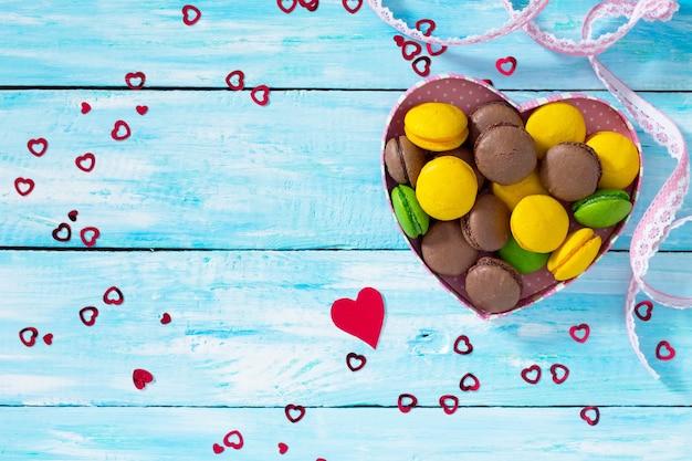 Composition de la saint-valentin avec des macarons dans un bol en forme de coeur sur une table en bois bleue. vue de dessus.
