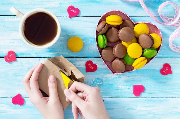 Composition de la saint-valentin avec des macarons dans un bol en forme de coeur et une tasse à café sur une table en bois bleue. mains déballage boîte-cadeau. vue de dessus.