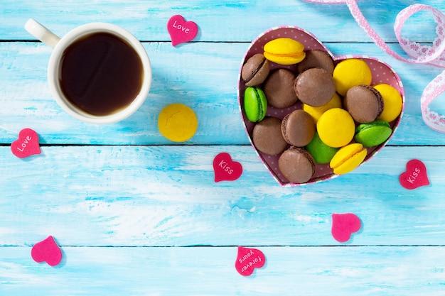 Composition de la saint-valentin avec des macarons dans un bol en forme de coeur et une tasse à café sur une table en bois bleue. vue de dessus.