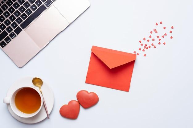 Composition de la saint-valentin. ordinateur de bureau féminin avec ordinateur portable, ñ up de thé et biscuit au gingembre comme coeur sur fond pastel. concept de la saint-valentin, design plat. vue de dessus