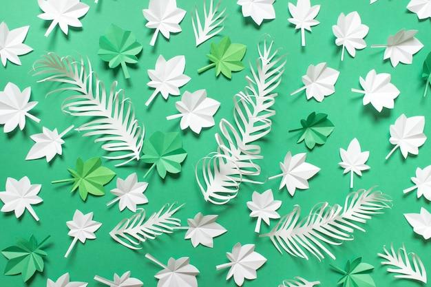 Composition de la saison du papier avec des feuilles d'érable blanc vert et des plumes de papier sur fond vert.