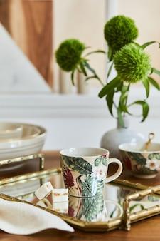Composition de salle à manger créative et élégante avec porcelaine élégante, plateau doré et beaux accessoires personnels. appartements de luxe. la beauté dans les détails. modèle.