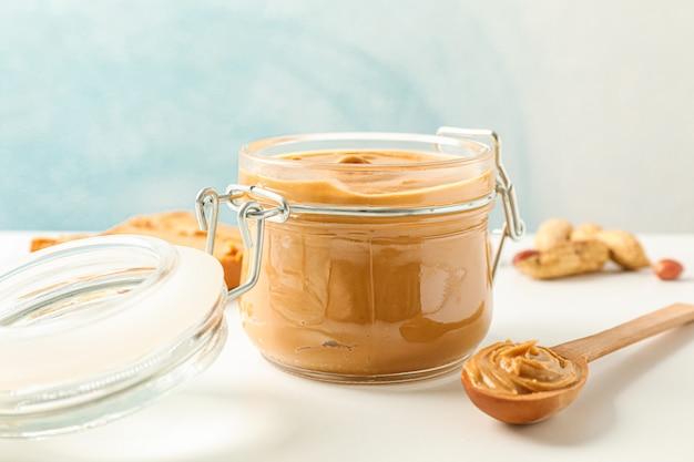 Composition avec sandwich au beurre d'arachide, bocal en verre, arachide et cuillère sur tableau blanc