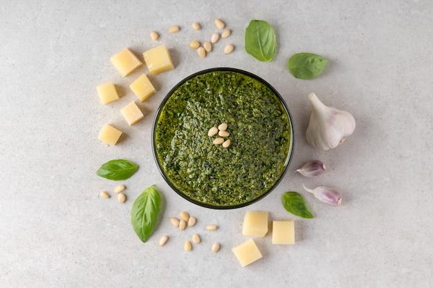 Composition avec sauce pesto verte dans un bol et ingrédients sur table grise