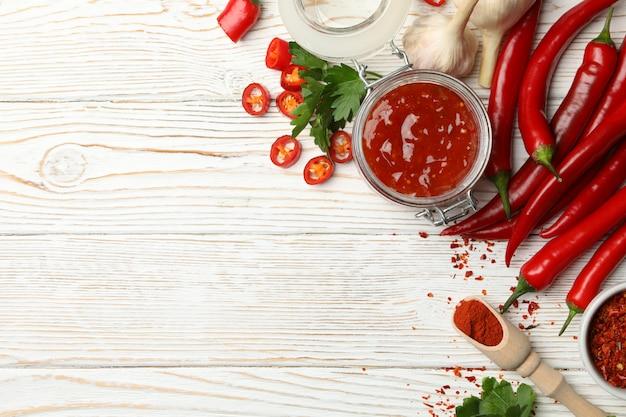 Composition avec sauce piquante rouge et ingrédients sur mur en bois