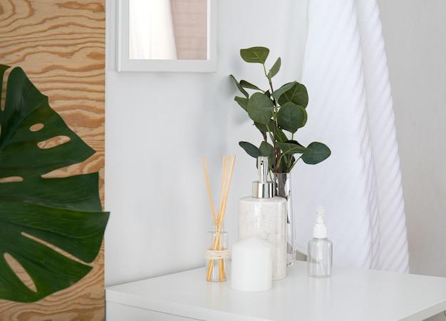 Composition de serviettes éponge et accessoires de salle de bain à l'intérieur. salle de bain fraîche et agréable avec des éléments en bois, des fleurs, des feuilles tropicales monstera et un miroir.