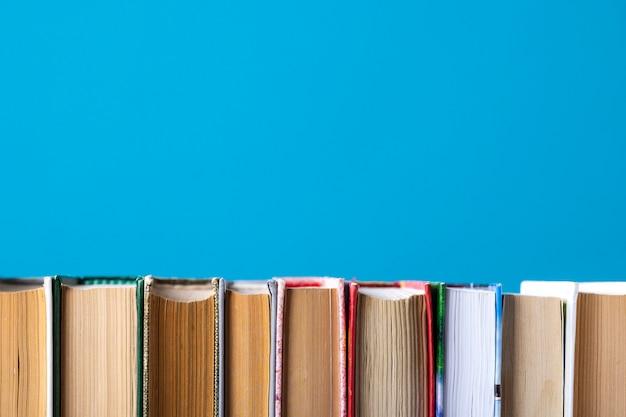 Composition simple de livres cartonnés, de livres bruts sur une table de terrasse en bois et bleue