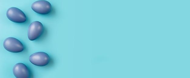 Composition simple avec des oeufs de pâques bleus sur fond coloré branché