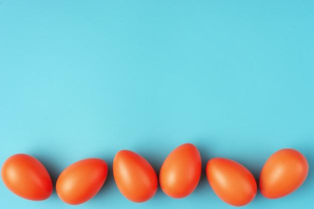 Composition simple avec des oeufs de pâques orange vif sur fond bleu-vert
