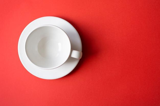 Composition simple à plat avec un bol de tasse en céramique blanche vide sur une assiette