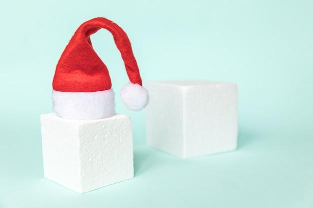 Composition simplement minimale hiver objet bonnet de noel et formes cubiques forme géométrique podium isolé bl...