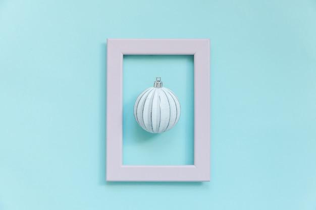 Composition simplement minimaliste objets d'hiver boule d'ornement dans un cadre rose isolé sur bleu pastel