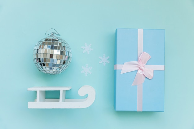 Composition simplement minime objets d'hiver ornement boule traîneau boîte cadeau isolé sur bleu pastel