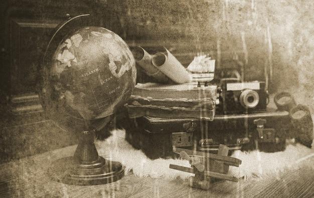 Composition sur un sol en bois globe vintage avec une vieille valise en cuir avec des objets de voyage