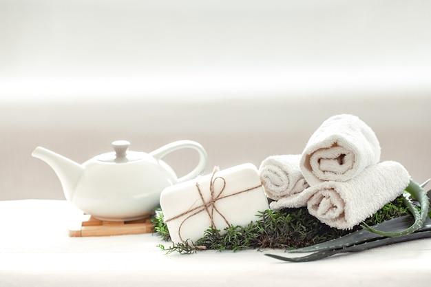 Composition de spa à l'aloe vera sur la lumière avec une serviette blanche torsadée.