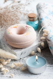 Composition de spa avec beignets de bombe de bain et fleurs sèches sur fond rustique dans un style monochrome. bougies et sel. traitement de beauté et détente