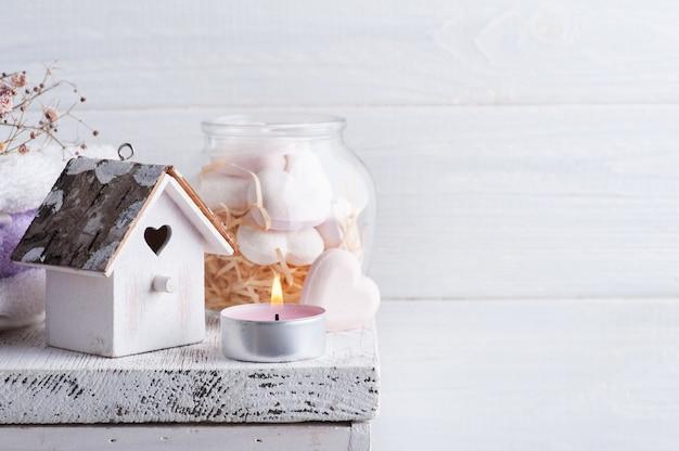 Composition de spa avec des coeurs de bombe de bain et des fleurs sèches sur fond rustique dans un style monochrome. bougies et serviettes. traitement de beauté et détente