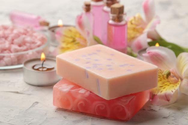 Composition de spa avec du savon artisanal gros plan sur béton gris et blanc