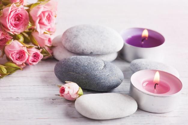Composition de spa avec des fleurs roses, des bougies allumées