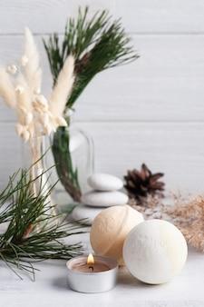 Composition de spa de noël avec des bombes de bain et des branches de pin et une bougie allumée. beauté bien-être, soins cosmétiques pour le corps. carte de voeux pour la fête des mères, noël ou mariage