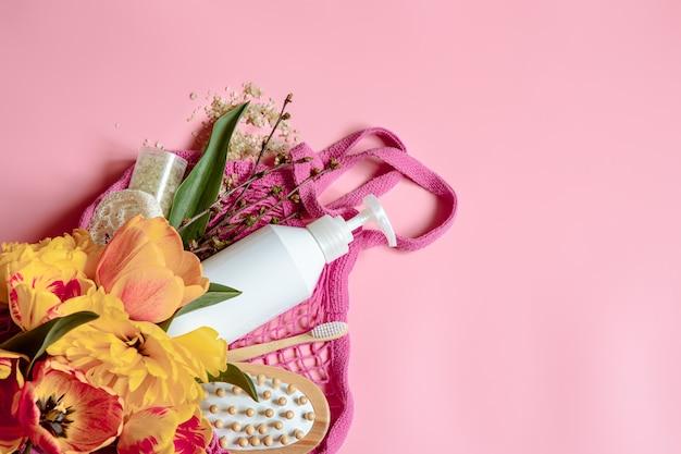 Composition de spa à plat avec fleurs et accessoires de bain dans un sac à cordes.